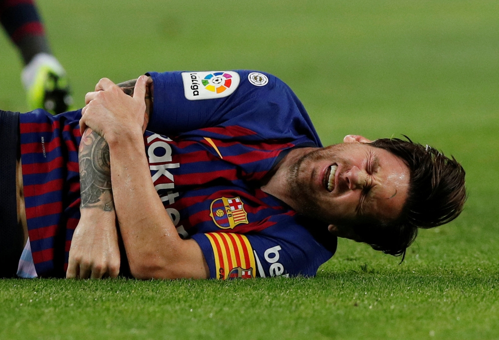 Barcelona's Lionel Messi writhing on the ground after sustaining injury during their La Liga match against Sevilla at Camp Nou, Barcelona, Saturday. — Reuters