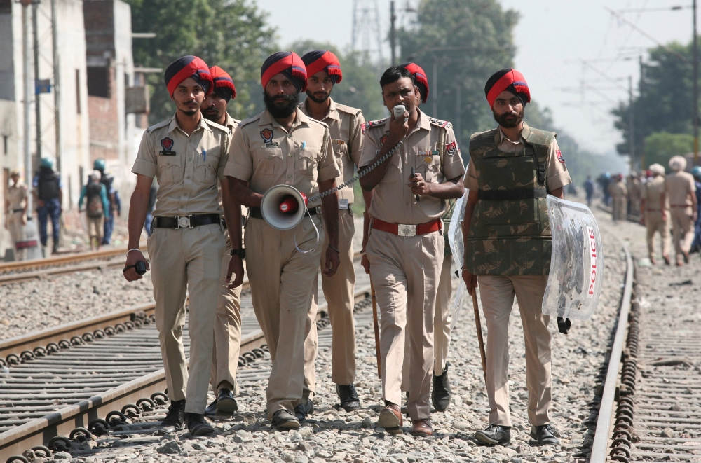 A policeman on Sunday speaks over a megaphone asking people to stay away from the railway track after a commuter train travelling at high speed ran over a crowd in Amritsar, India, on Friday. — Reuters