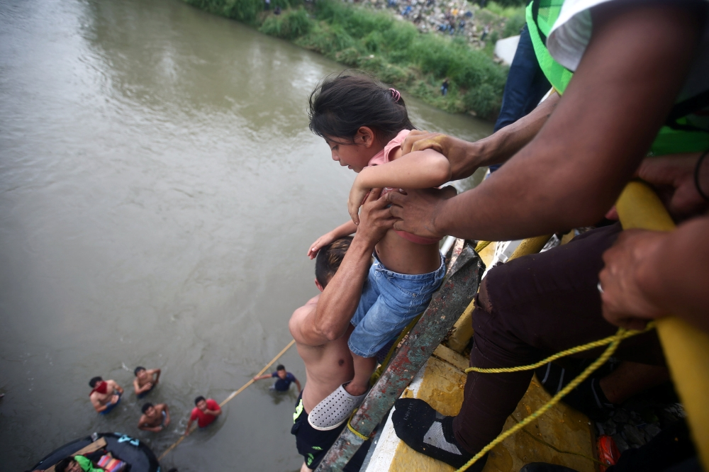 Central American migrant, part of a caravan trying to reach the US, holds a child as he goes down from a bridge that connects Mexico and Guatemala to avoid the border checkpoint in Ciudad Hidalgo, Mexico, Saturday. — Reuters