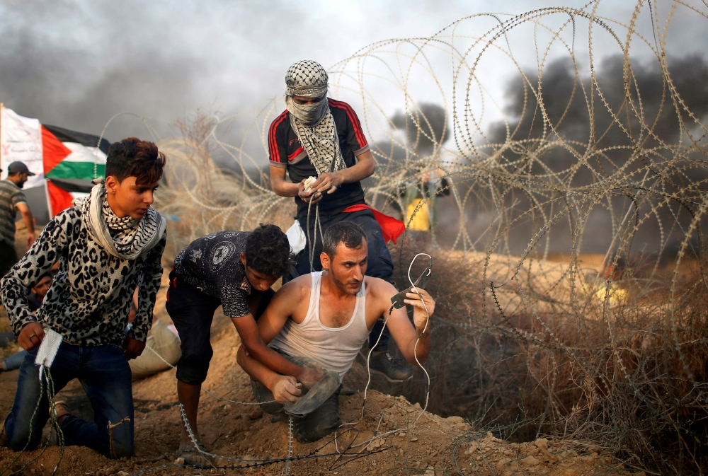A disabled Palestinian is helped as he uses a sling to hurl stones at Israeli troops during a protest calling for lifting the Israeli blockade on Gaza and demanding the right to return to their homeland, at the Israel-Gaza border fence in Gaza. — Reuters