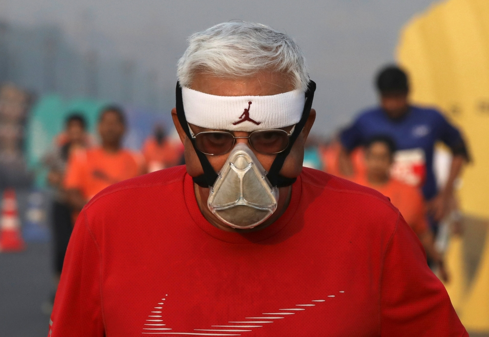 A runner wearing a face mask for protection from air pollution takes part in the Delhi Half Marathon in New Delhi on Sunday. — Reuters