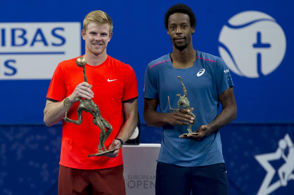Britain's Kyle Edmund holds his trophy after beating France's Gael Monfils (R) in the final of the 'European Open' hard court tennis tournament in Antwerp Sunday. — AFP
