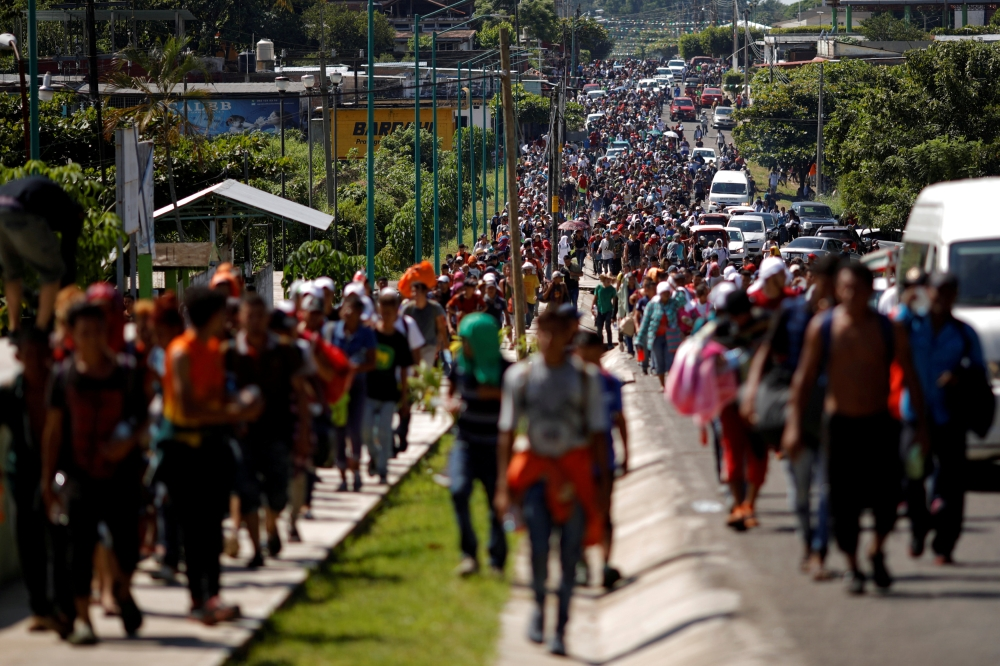 Central American migrants walk along the highway near the border with Guatemala, as they continue their journey trying to reach the US, in Tapachula, Mexico, on Sunday. — Reuters