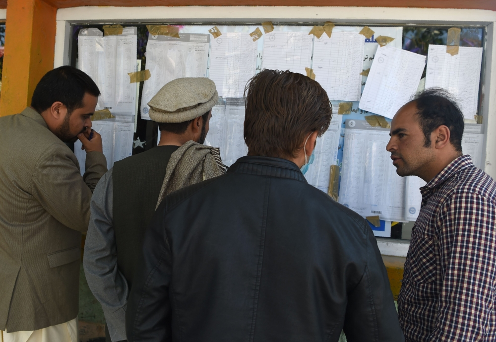 Afghan election observers check the voting results put on display at a polling center after ballots in the country's legislative election were counted in Kabul on Monday. — AFP