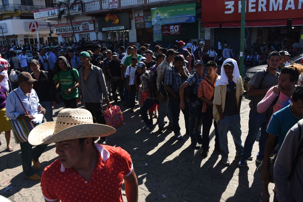 Honduran migrants taking part in a caravan heading to the US queue to receive food donations at the main square in Tapachula, Chiapas state, Mexico, on Monday. — AFP