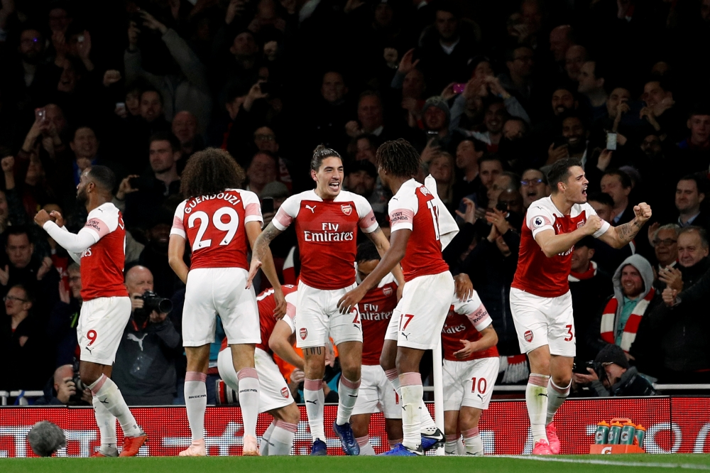 Arsenal players celebrate their third goal against Leicester during their Englaish Premier League match Monday. — AFP