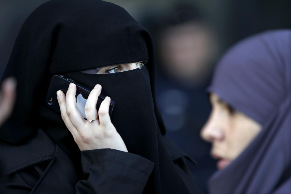 A women wearing a niqab makes a phone call outside the courts in Meaux, east of Paris. — Reuters file photo