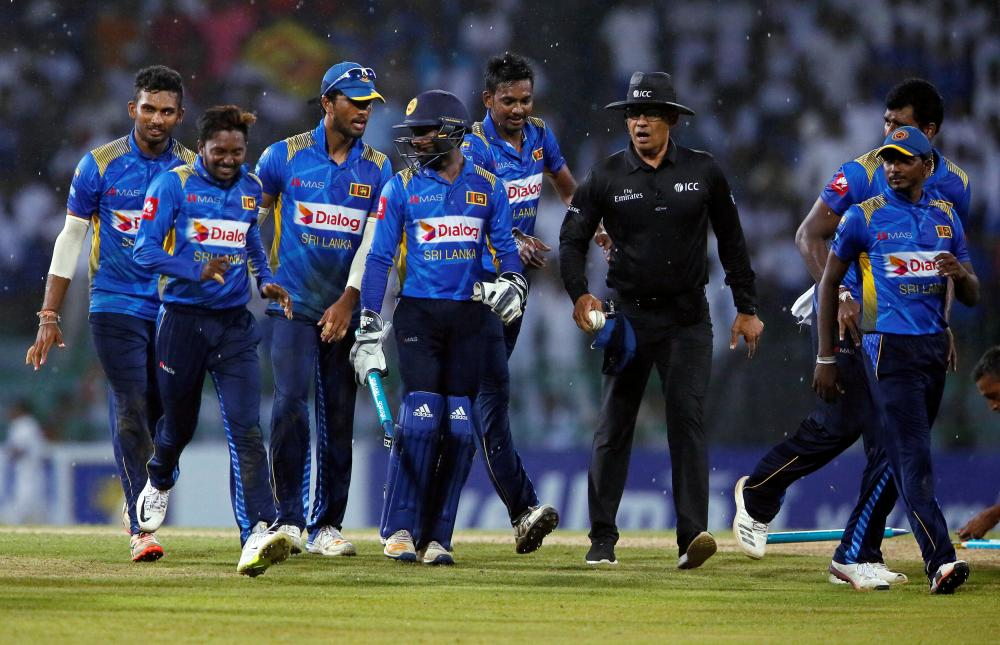 Sri Lanka's captain (3rd L) and his teammates walk off the field as the match was stopped due to rain against England during the fifth One-Day International match at Colombo Tuesday. — Reuters.