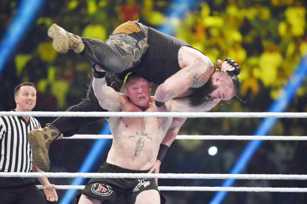 Brock Lesnar performs his F5 move on Braun Strowman during the WWE Universal Championship match at the WWE Crown Jewel show at the King Saud University Stadium in Riyadh Friday. — AFP