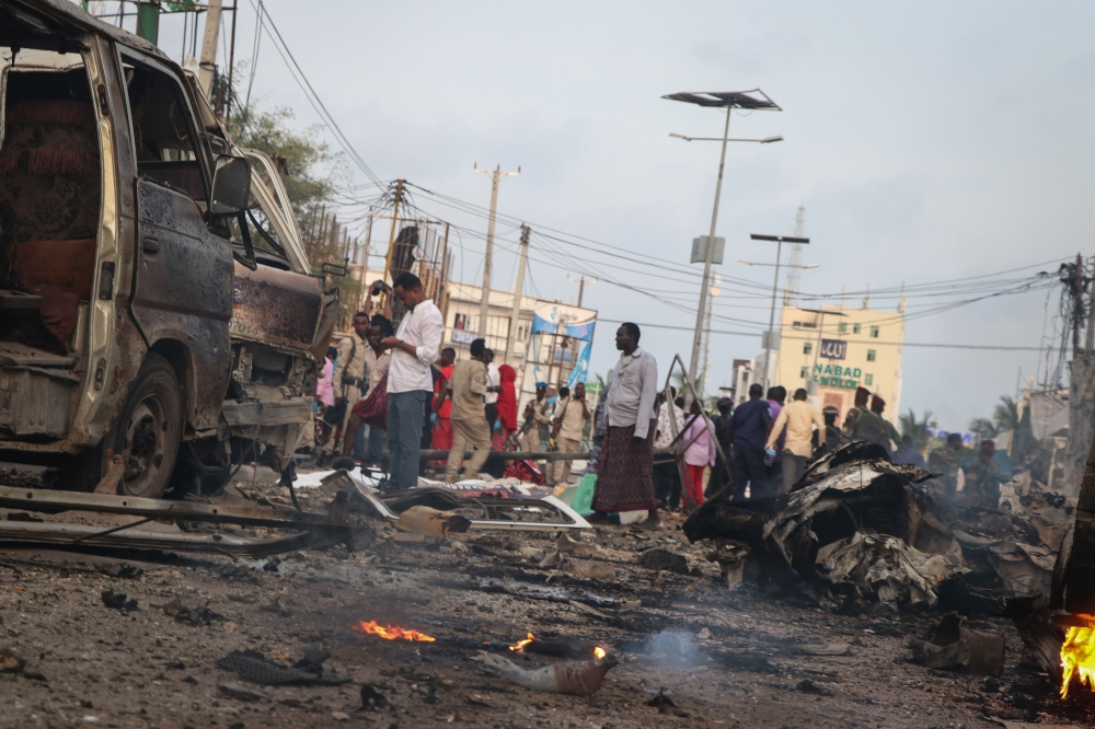 People gather at the scene of twin car bombs that exploded within moments of each other in the Somali capital Mogadishu on Friday. — AFP