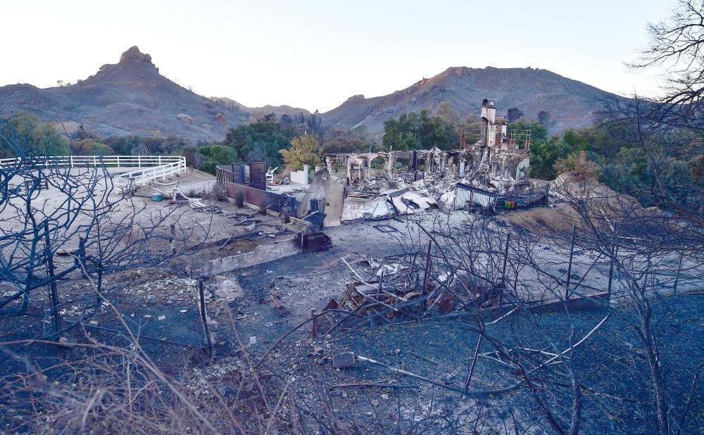 The remnants of a home destroyed in the Woolsey fire are seen along Mulholland Highway in the hills above Malibu, California, on Monday. — AFP