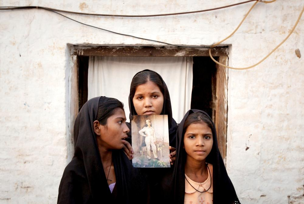 The daughters of Pakistani Christian woman Asia Bibi pose with an image of their mother while standing outside their residence in Sheikhupura, Pakistan, in this Nov. 13, 2010 file photo. — Reuters