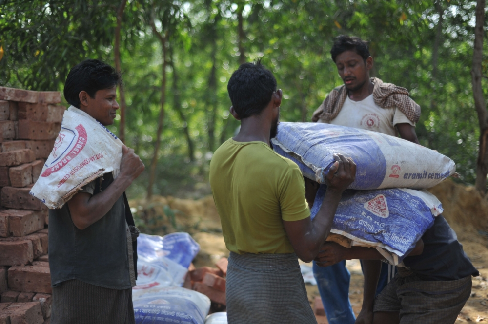 Rohingya construction workers carry bags of cement at an under-construction repatriation center in Ghumdhum near Naikhongchhari in Bangladesh's Bandarban district on Monday. — AFP