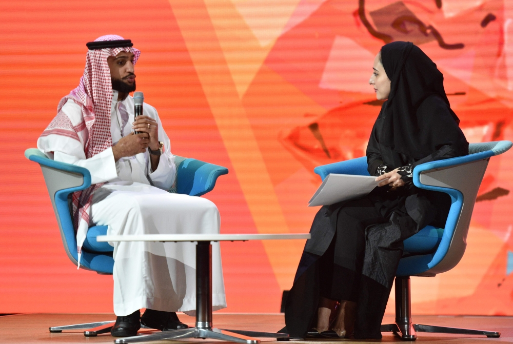 "First Saudi female Olympic fencer Lobna Al-Omair speaks with British professional boxer Amir Khan on the panel ""What defines me"". Amir attended the session wearing the traditional Saudi attire. — SG"