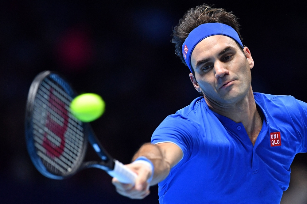 Switzerland's Roger Federer returns against Germany's Alexander Zverev during their men's singles semifinal match on day seven of the ATP World Tour Finals tennis tournament at the O2 Arena in London on Saturday. — AFP