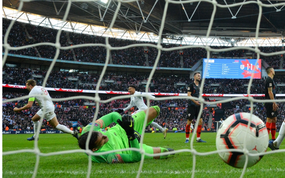 England's striker Harry Kane (L) celebrates after his shot beats Croatia's goalkeeper Lovre Kalinic (C) for their second goal during the international UEFA Nations League football match between England and Croatia at Wembley Stadium in London on Sunday. England beat Croatia 2-1 to qualify for the Nations League semifinals. — AFP