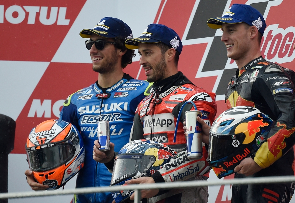 Race winner Ducati Team's Italian rider Andrea Dovizioso (C) celebrates on the podium with second placed Team Suzuki Ecstar's Spanish rider Alex Rins (L) and third placed Red Bull KTM Factory Racing's Spanish rider Pol Espargaro after the MotoGP race of the Valencia Grand Prix at the Ricardo Tormo racetrack in Cheste, on Sunday. — AFP