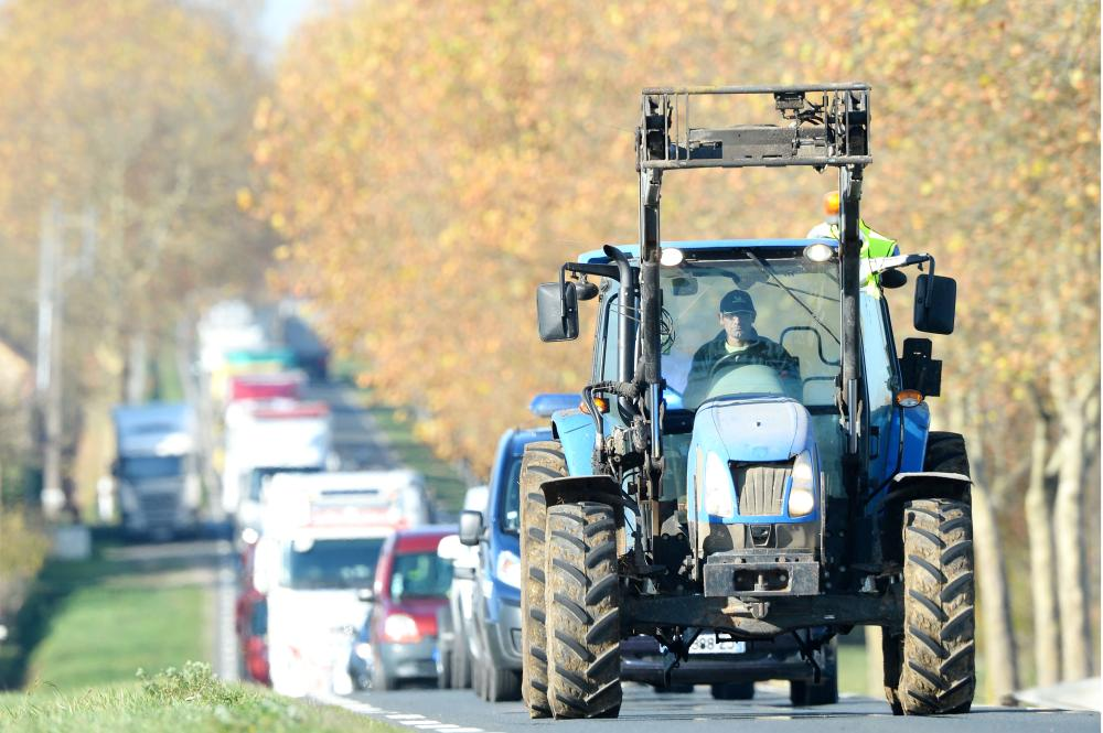 A tractor drives with yellow vest (gilet jaune) as a dozen farmers take part in an operation to slow the traffic, between Saint Calais and Epuisay, on the D157 or Orleans-Blois road on Monday on the third day of nationwide protest against high fuel prices. — AFP