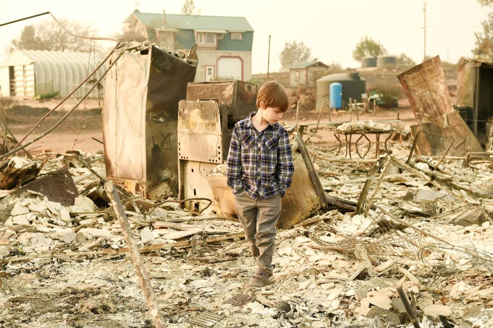 Jacob Saylors, 11, walks through the burned remains of his home in Paradise, California, on Sunday. — AFP