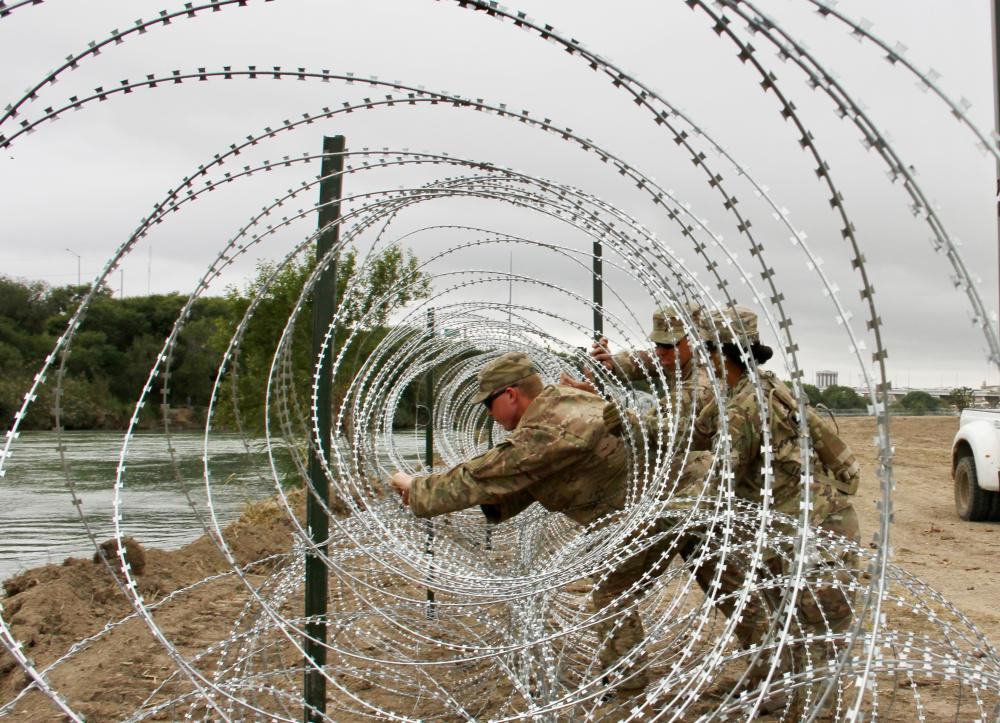 Soldiers from the Kentucky-based 19th Engineer Battalion are installing barbed wire fences on the banks of the Rio Grande in Laredo, Texas, on Sunday. — AFP