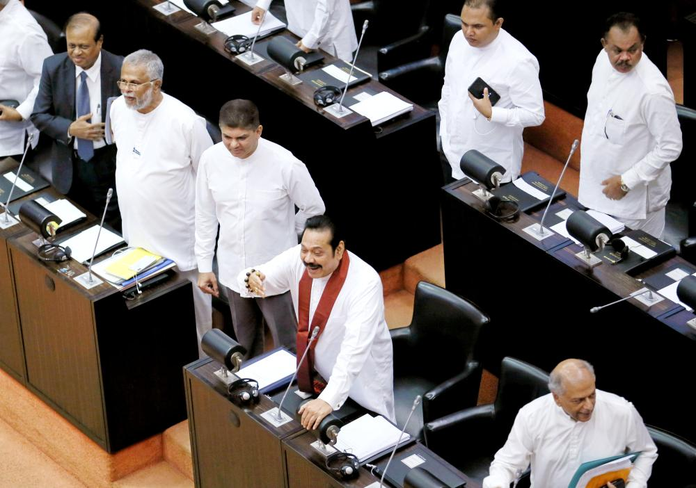 Sri Lanka's newly appointed Prime Minister Mahinda Rajapaksa makes a joke towards opposition parties seats at the parliament in Colombo on Monday. — Reuters