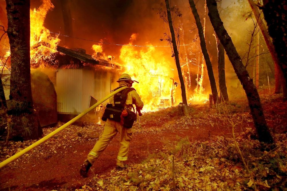 A firefighter pulls a hose toward burning home as the Camp Fire moves through the area on  in Magalia, California, in this Nov. 9, 2018 file photo. — AFP