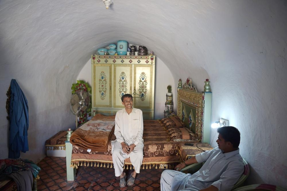 Pakistani villager Ameer Ullah Khan, left, chats with a friend in his cave room in Nikko village, about 60 km from the capital Islamabad, near  the highway town Hasan Abdal in this Oct. 6, 2018 file photo. — AFP
