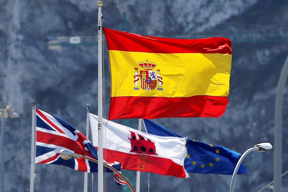 A Spanish flag, top, British union flag, left, the Gibraltarian flag, center, and the European Union flag fly at the border of Spain with the British territory of Gibraltar, historically claimed by Spain, as they are seen from La Linea de la Concepcion, Spain, in this April 18, 2018 file photo. — Reuters