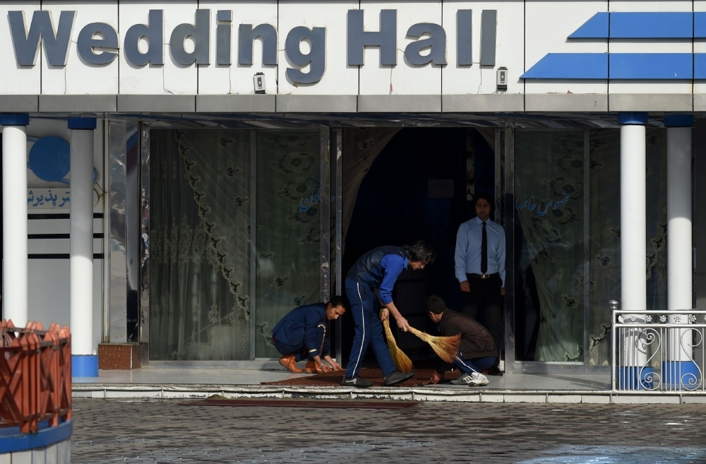 Afghan workers clean the area outside of a wedding hall a day after a deadly suicide attack in Kabul on Wednesday. — AFP