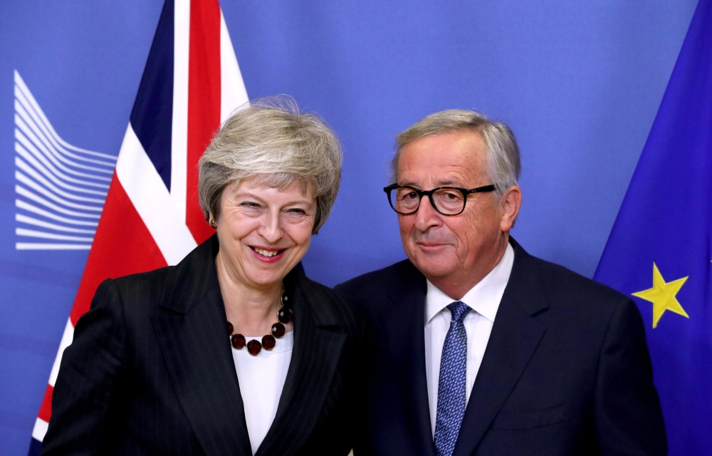 British Prime Minister Theresa May and with European Commission President Jean-Claude Juncker meet to discuss draft agreements on Brexit, at the EC headquarters in Brussels, Belgium, on Wednesday. — Reuters