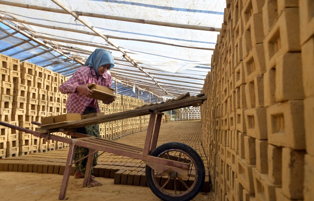This photo taken on Wednesday shows Myanmar woman working in a brick factory in Naypyidaw. —  AFP