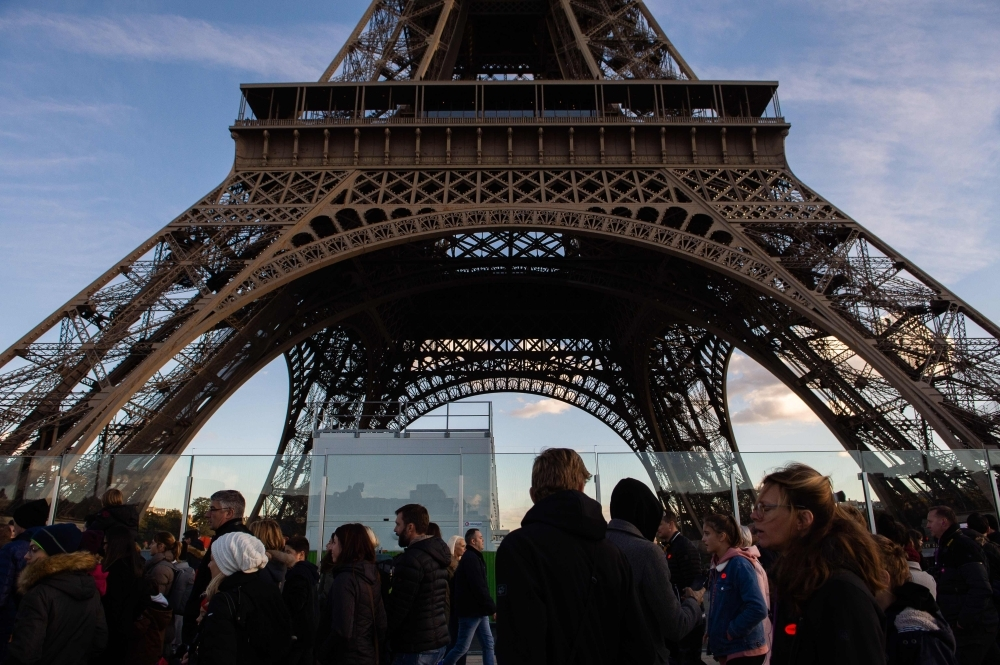 In this file photo, people are seen walking along the Eiffel tower in Paris. The Eiffel Tower will be closed on Dec. 8, 2018 amid 'yellow vest' protests planned on the same day in Paris. — AFP