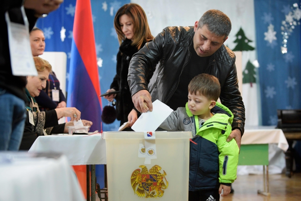 A man casts his ballot with his son as part of early parliamentary elections in Yerevan, Sunday. — AFP