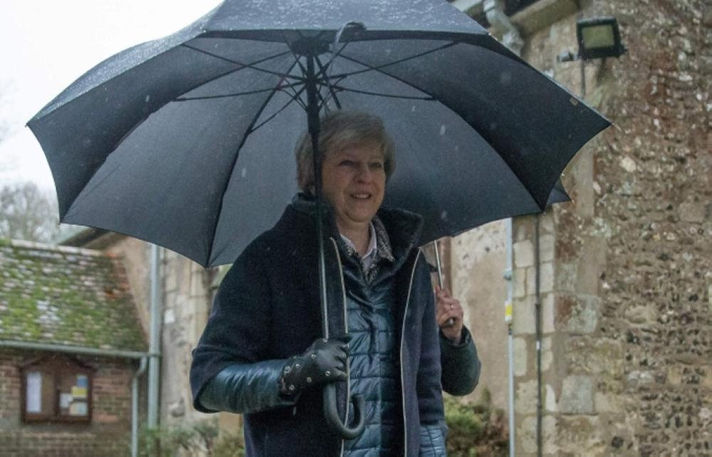 Britain's Prime Minister Theresa May shelters from the rain under an umbrella after attending a church service near to her Maidenhead constituency, west of London, Sunday. — AFP