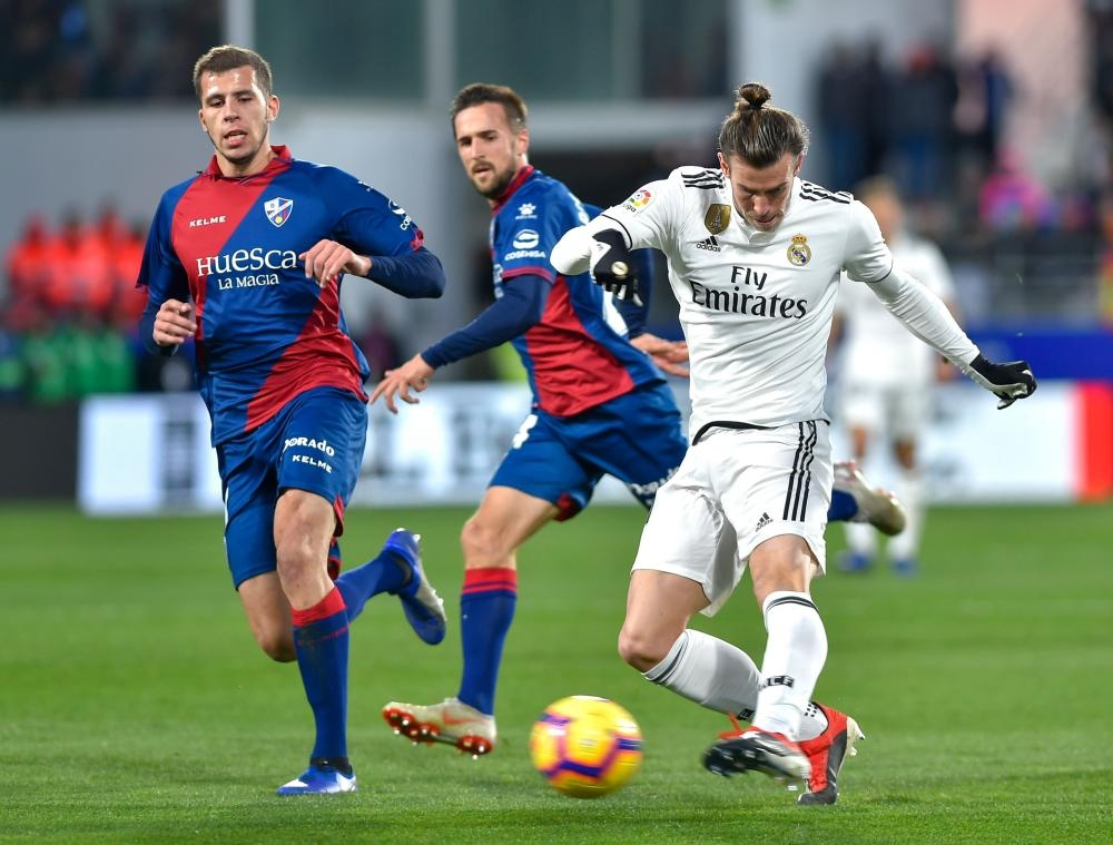 Real Madrid's Gareth Bale (R) kicks the ball during the Spanish league football match against SD Huesca at the El Alcoraz Stadium in Huesca Sunday. — AFP