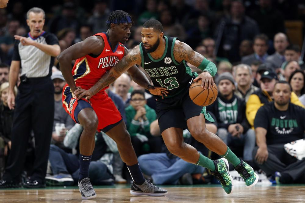 Boston Celtics' forward Marcus Morris drives against New Orleans Pelicans' guard Jrue Holiday during their NBA game at TD Garden in Boston Monday. — Reuters