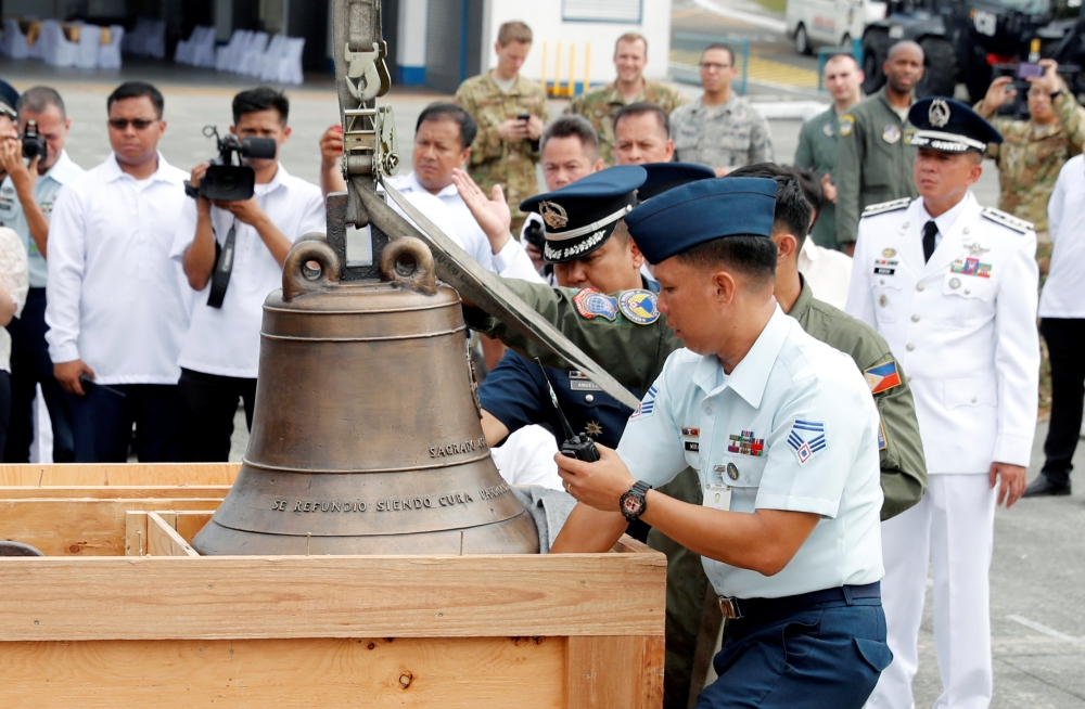 Philippine Air Force personnel unload the bells of Balangiga after their arrival at Villamor Air Base in Pasay, Metro Manila, Philippines, on Tuesday. — Reuters