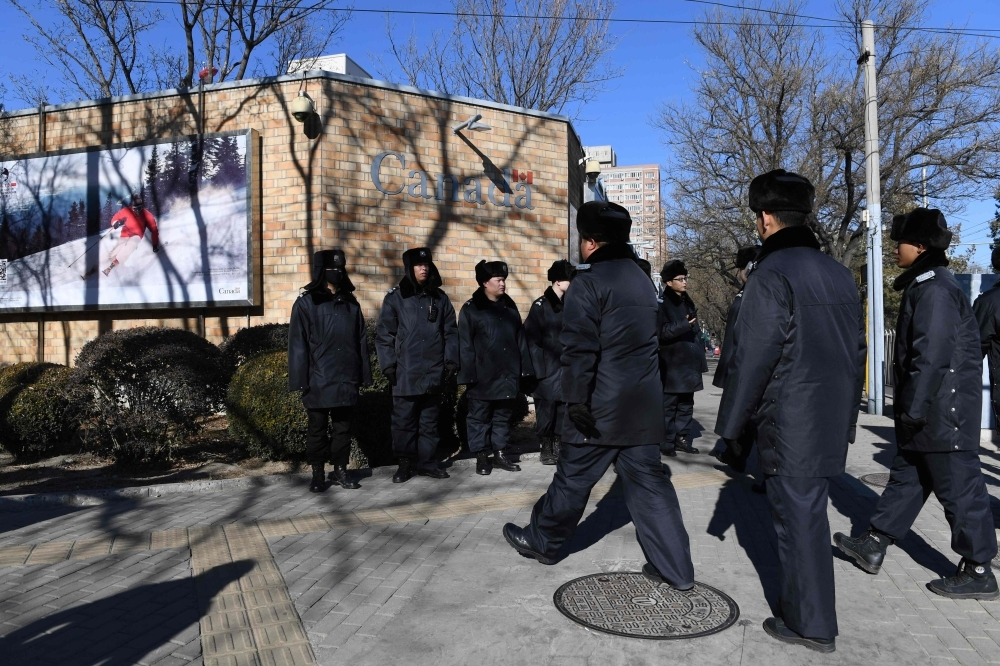 Chinese police patrol in front of the Canadian embassy in Beijing on Thursday. — AFP