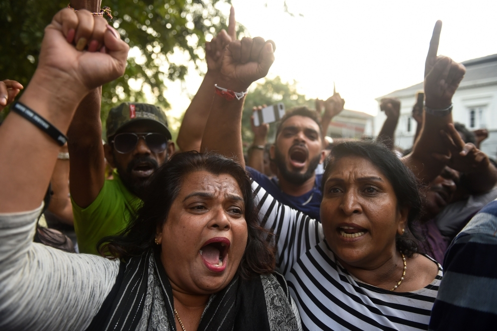 Supporters of ousted Sri Lankan Prime Minister Ranil Wickremesinghe shout slogans as they celebrate the top court's ruling outside the Sri Lankan Supreme Court in Colombo on Thursday. — AFP