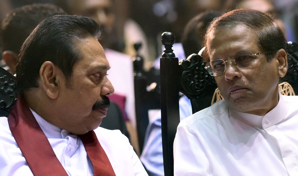 Sri Lankan President Maithripala Sirisena, right, listens to former president and currently-appointed Prime Minister Mahinda Rajapaksa during a ceremony granting employment to social service workers in Colombo in this Nov. 30, 2018 file photo. — AFP