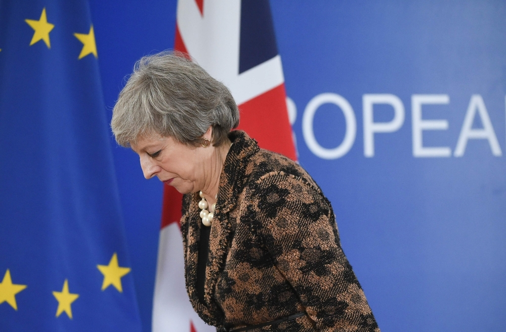 Britain's Prime Minister Theresa May leaves after speaking during a press conference on Friday in Brussels during the second day of a European Summit aimed at discussing the Brexit deal, the long-term budget and the single market. — AFP