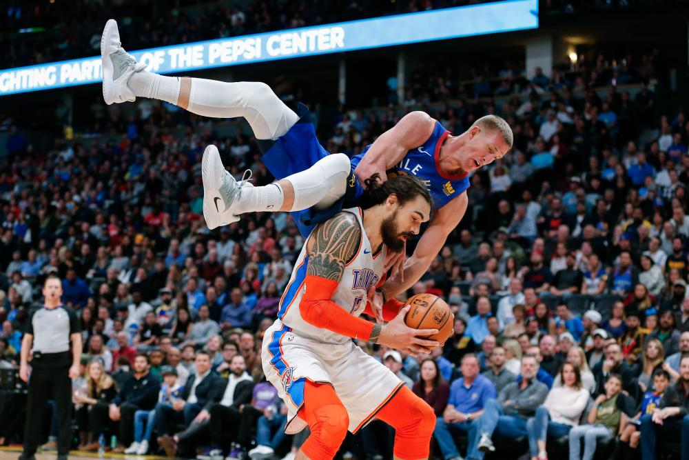 Denver Nuggets' forward Mason Plumlee falls over the back of Oklahoma City Thunder's center Steven Adams during their NBA game at the Pepsi Center in Denver Friday. — Reuters