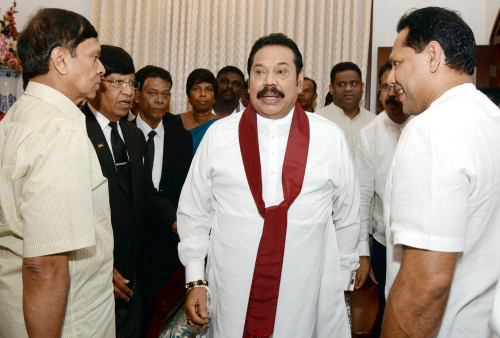 Sri Lanka's former leader Mahinda Rajapaksa shares a moment with his political party supporters after he resigned from the prime minister post in Colombo, Saturday. — Reuters