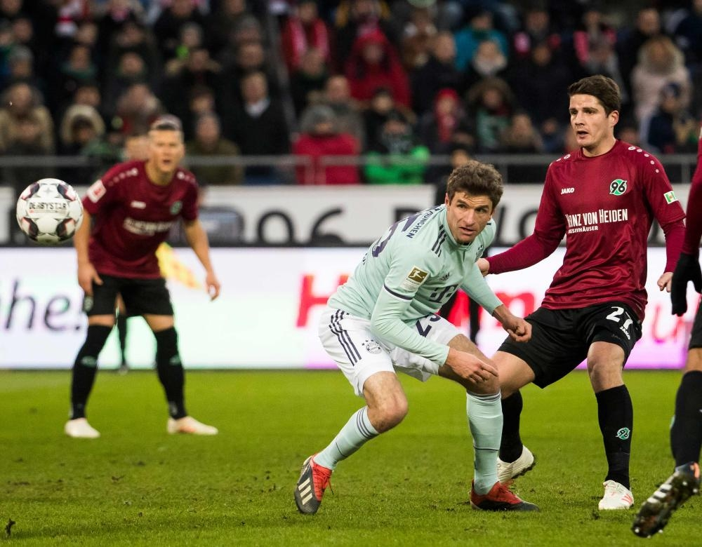 Bayern Munich's Thomas Mueller (C) and Hanover's Pirmin Schwegler vie for the ball during the German first division Bundesliga football match at the HDI arena in Hanover Saturday. — AFP