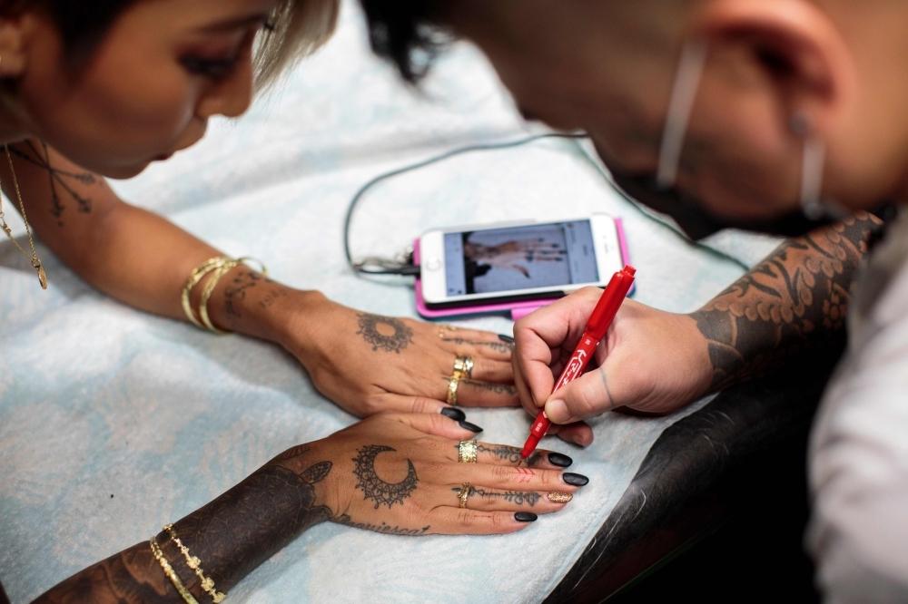 A woman gets a new tattoo design on her fingers at a tattoo studio in Tsurugashima, Saitama prefecture. — AFP