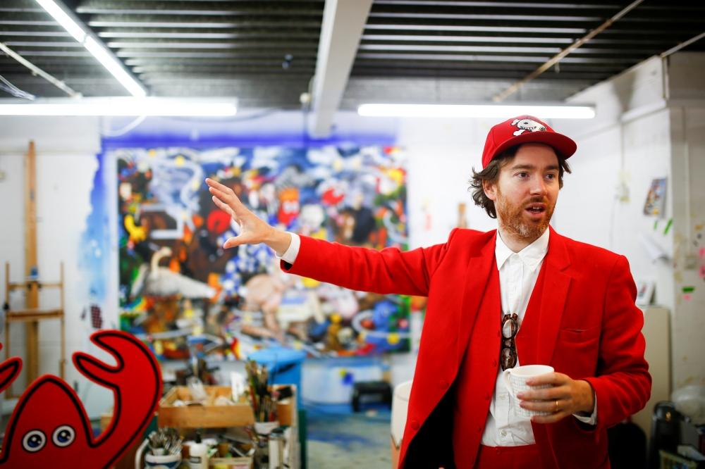 Fashion designer and artist Philip Colbert gestures at his studio in Shoreditch, London. — Reuters
