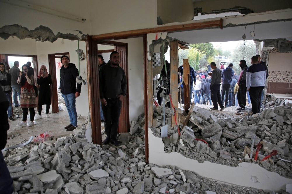 Palestinians inspect the flat of Ashraf Naalwa after Israeli forces destroyed it in the village of Shuwaykah, near the West Bank city of Tulkarem, on Monday. — AFP