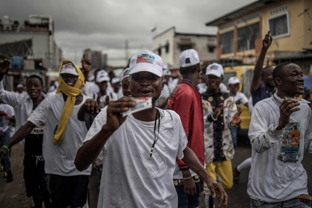 A crowd campaigns under a downpour for a candidate to the Congolese parliament, Christian Ngelebeya Papy, on Monday, in Kinshasa. — AFP