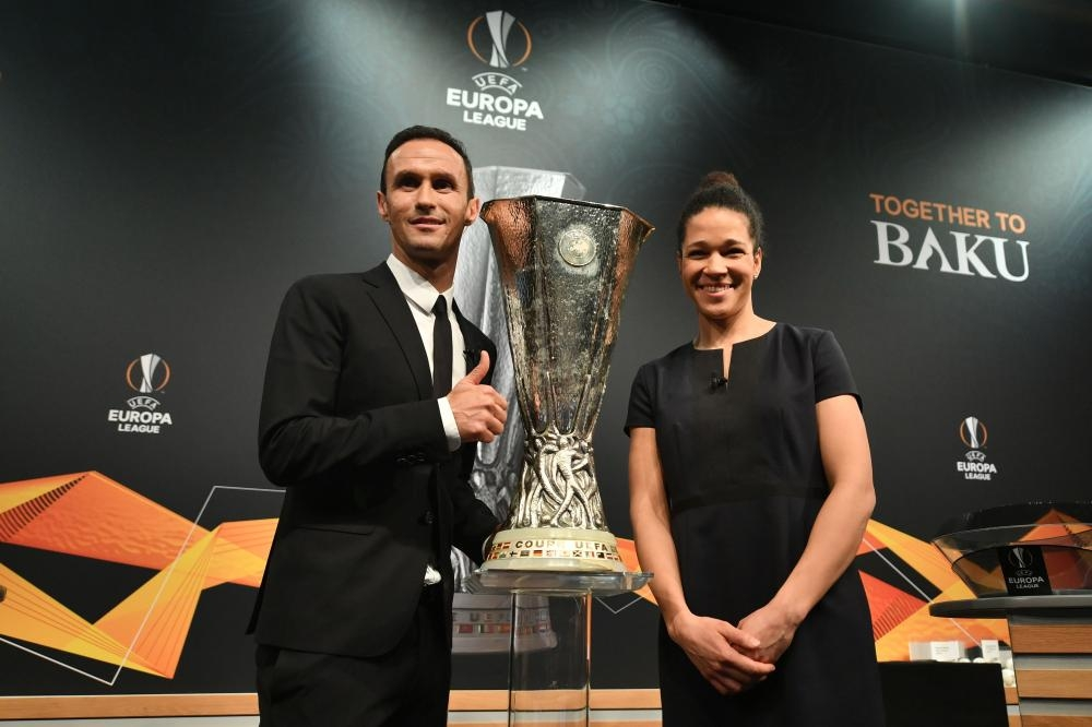 Former German football Celia Sasic (R) and Former Portuguese football player Ricardo Carvalho pose with the cup after the draw for the round of 32 of the UEFA Europa League football tournament at the UEFA headquarters in Nyon Monday. — AFP