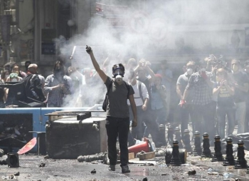 A Turkish protester wears a gas mask and holds a stone as demonstrators face riot police. — File photo